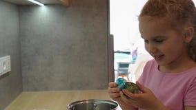 惊奇白肤金发的女孩看看被绘的五颜六色的复活节彩蛋和照相机 r 影视素材