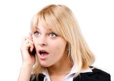 惊奇白肤金发的女孩联系在电话 免版税库存图片