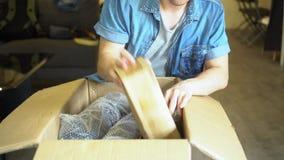 惊奇的亚裔人箱中取出的包裹在家 影视素材