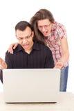 惊奇的偶然看膝上型计算机的男人和妇女 免版税库存图片