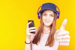 惊奇的十几岁的女孩使用耳机和手机 图库摄影