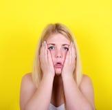 惊奇的女孩画象反对黄色背景的 免版税库存图片