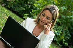 惊奇的女实业家谈话在手机,当使用膝上型计算机本质上时 库存照片