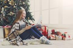 惊奇的妇女在网上在圣诞节内部的膝上型计算机的 免版税库存图片