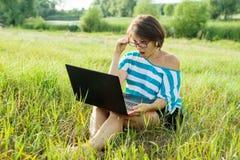 惊奇的妇女看膝上型计算机显示器 妇女自由职业者,工作本质上,在公园 免版税库存照片
