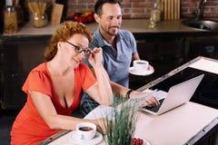 惊奇的妇女读书新闻在厨房里 免版税图库摄影