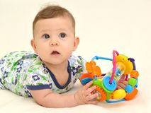 惊奇的婴孩的画象有一个玩具的在轻的背景 库存照片
