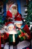 惊奇的孩子打开不可思议的圣诞节礼物 库存图片