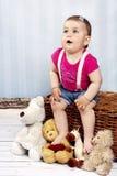 惊奇的小小孩坐与长毛绒的篮子戏弄 图库摄影