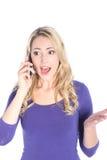 惊奇的新白肤金发的妇女联系在移动电话 库存照片