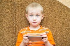 惊奇的男孩在手上的拿着一个智能手机 库存照片