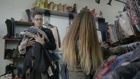 惊奇的男朋友伴随他的女朋友做购物并且拿着她要-的所有衣裳 股票录像