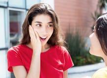 惊奇的白种人女孩讲话与女朋友 免版税库存图片