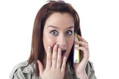 惊奇的白种人女孩说在电话里 库存图片