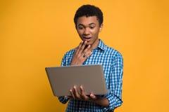 惊奇的美国黑人的青少年的看看膝上型计算机屏幕 库存照片