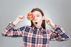 惊奇的逗人喜爱的十几岁的女孩用棒棒糖盖了她的眼睛 免版税库存照片