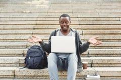惊奇的非裔美国人的学生坐台阶使用膝上型计算机 免版税图库摄影