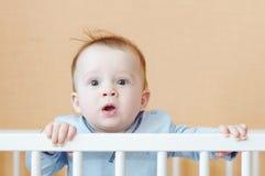 惊奇的婴孩在白色床上 图库摄影