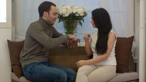 惊奇英俊的人他的有一件礼物的女朋友在家在客厅 股票录像