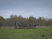 惨淡的被放弃的倒塌的农场流洒与多云天空 库存照片