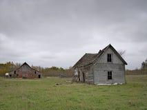 惨淡的被放弃的被毁坏的农厂议院和谷仓有多云天空的 库存图片