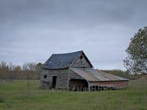 惨淡的被放弃的被毁坏的农场流洒与多云天空 免版税库存照片