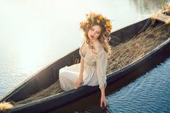 幻想在小船的一个美丽的夫人的艺术照片 免版税库存图片