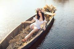 幻想在小船的一个美丽的夫人的艺术照片 免版税库存照片