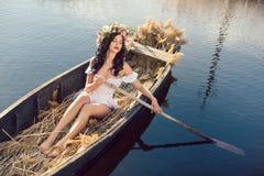 幻想坐在小船的一个美丽的女孩的艺术照片 免版税库存照片