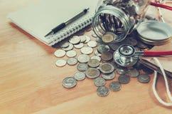 想法保存的金钱和听诊器在硬币医疗的healhcare的 库存照片