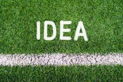 想法手在足球场草的文字文本 库存图片