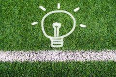 想法电灯泡在足球场草的手图画 免版税库存图片