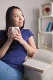 想法的亚裔妇女坐拿着杯子咖啡的长沙发 库存图片