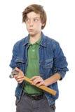 想法的十几岁的男孩在他的手上的拿着一把锤子  免版税库存图片