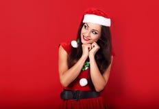 想法的愉快的妇女在圣诞老人圣诞节打扮看  库存照片