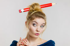 想法的白肤金发的妇女有大铅笔在头发 库存图片