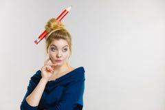 想法的白肤金发的妇女有大铅笔在头发 图库摄影