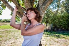想法的50s妇女在乡情隐喻的树下  免版税库存照片
