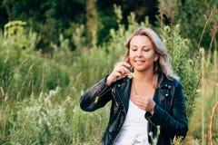 想知道在一朵雏菊的女孩在夏天草甸 免版税库存图片