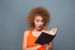 想知道的卷曲年轻女性阅读书 库存图片