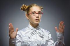 想知道的女孩 特写镜头画象英俊青少年在偶然在灰色背景的衬衣展示大大小孤立 免版税库存图片
