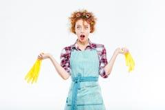 想知道的主妇在两只手中的拿着黄色手套 免版税库存照片