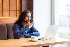 想知道英俊的有胡子的坐在咖啡馆和写书的便装样式的智力年轻成人人自由职业者画象  库存图片