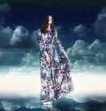 幻想 杂色的礼服的豪华妇女在蓝天 免版税图库摄影