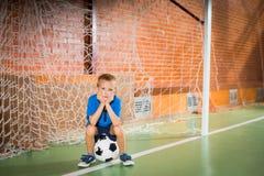 愁苦的年轻男孩坐的等待在球门柱 免版税库存照片