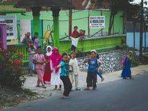 愉快一个小组印度尼西亚的孩子遇见外国游人 免版税图库摄影