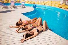 愉快三个女孩日光浴在水池附近 有吸引力的皮包骨头的g 免版税图库摄影