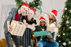 愉快三白种人男孩和的女孩和获得非洲的男孩微笑和在圣诞节庆祝的乐趣 库存图片