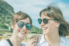 愉快两个的朋友微笑和 女孩纵向二年轻人 库存照片