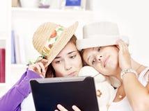愉快乐趣的女孩有少年触摸板使用 免版税库存图片